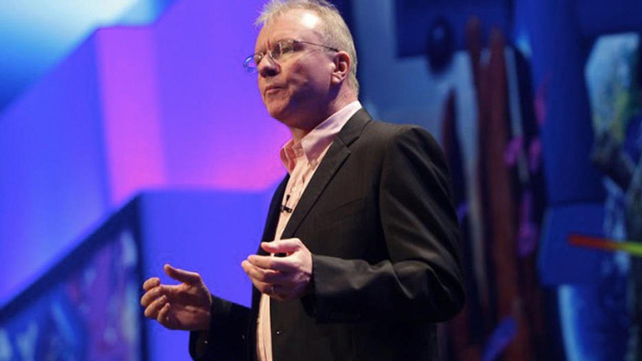 Jim Ryan, CEO da PlayStation, discursando de terno e gravata no palco de algum evento de games.