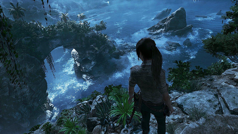 Tomb Raider: Lara Croft olhando de um penhasco para a praia ao fundo.