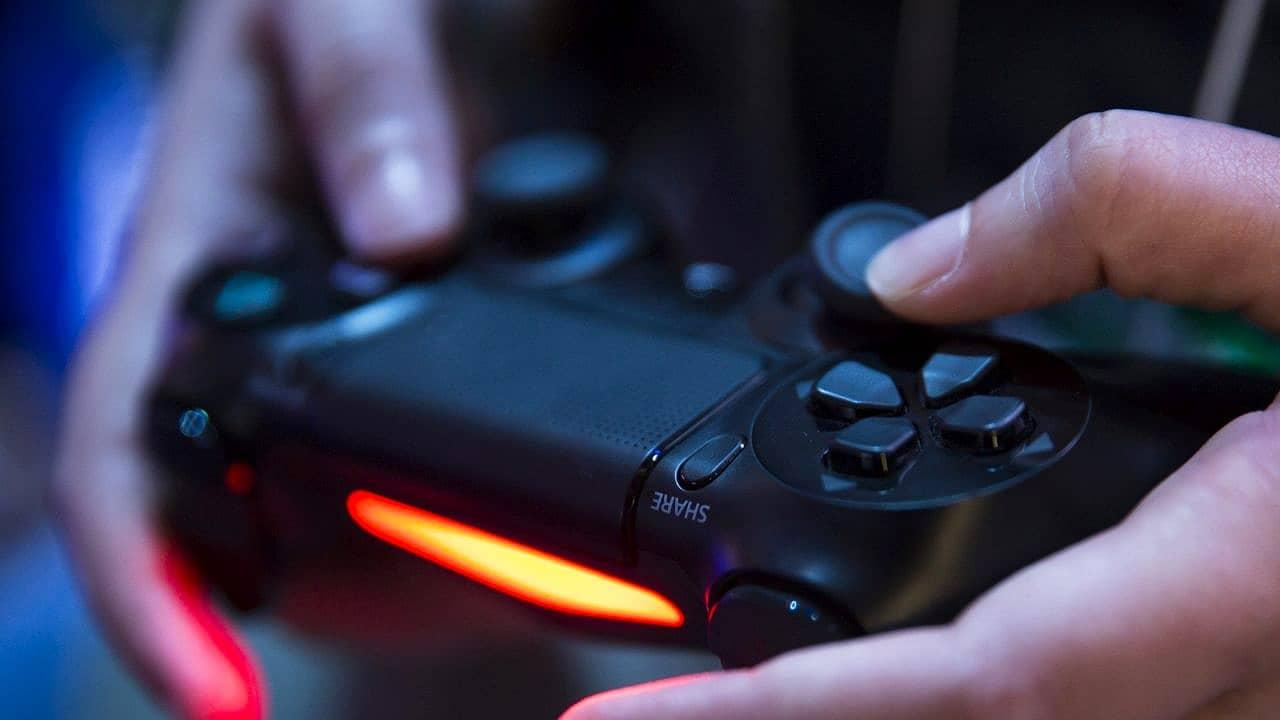 Imagem de uma pessoa segurando o controle DualShock 4, antecessor do DualSense