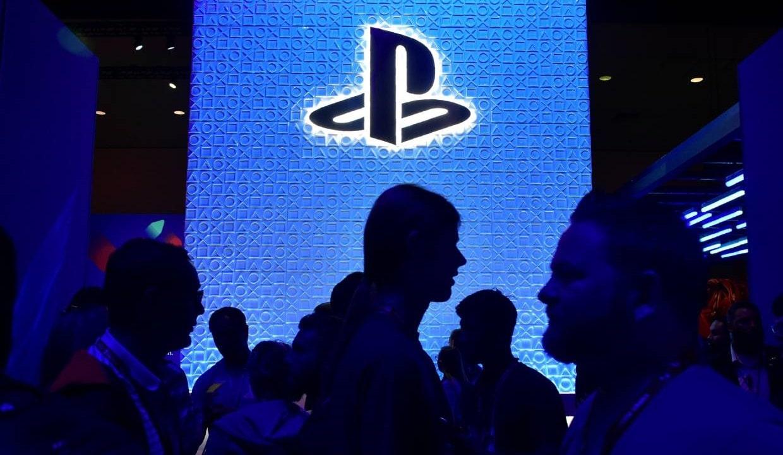 Stand da PlayStation durante uma conferência da E3 enquanto várias pessoas passam na frente do logo da marca.