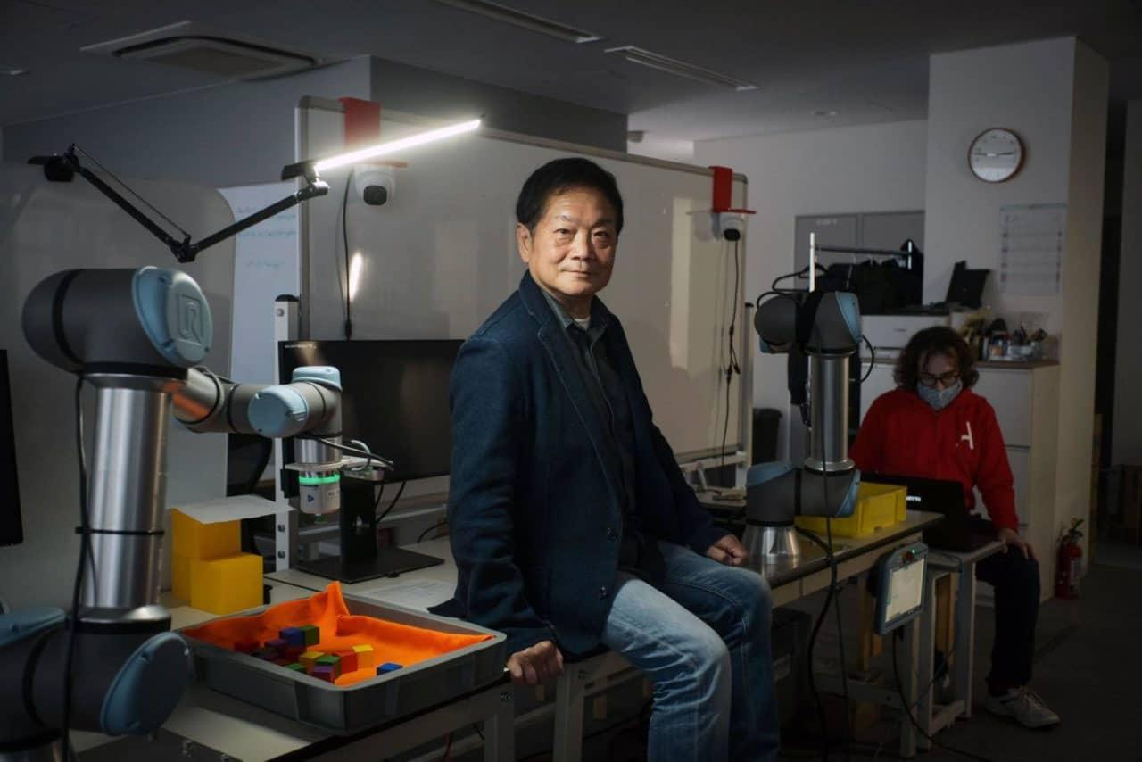 Ken Kutaragi, criador da PlayStation, sentado em uma bancada.