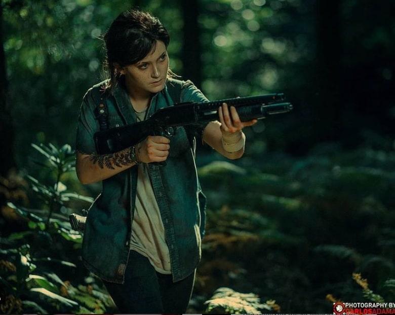 Cosplay de Ellie de The Last of Us Part II no meio da mata empunhando uma espingarda.