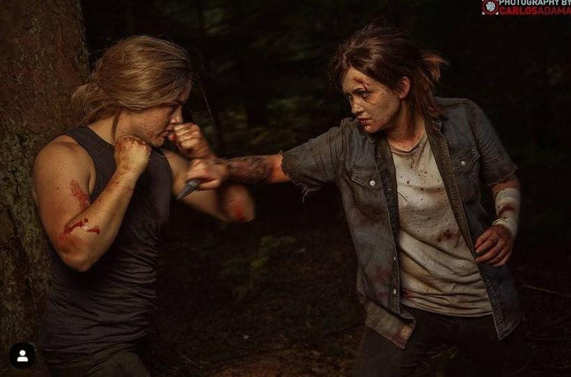 Cosplays de Abby e Ellie de The Last of Us Part II simulando uma briga do jogo.