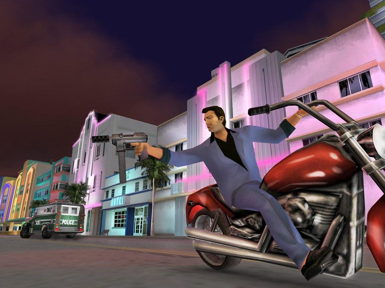 Tommy Vercetti, de GTA Vice City, jogo de PlayStation 2, em uma moto enquanto aponta uma metralhadora para alguém.