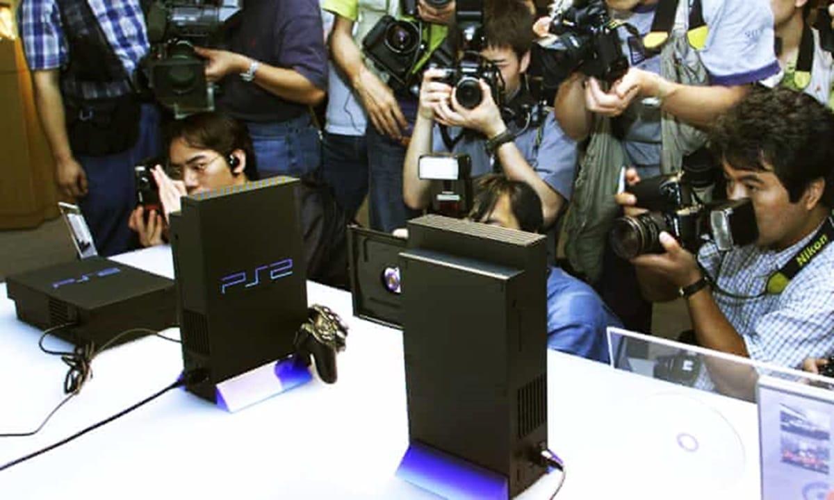 Evento de anuncio do PlayStation 2, com consoles em uma bancada branca e vários fotógrafos tirando fotos.