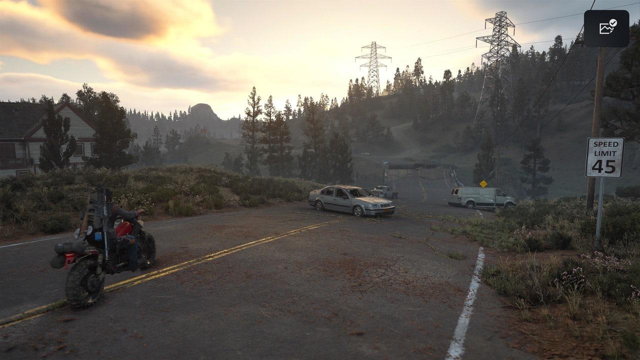 Imagem do protagonista de Days Gone sentado em sua moto no meio de uma rua com carros na sua frente e um cenário pós-apocalíptico