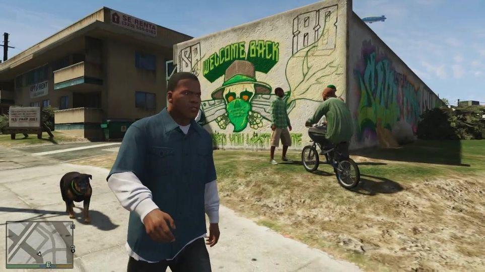 Franklin, personagem em GTA V, passeando pela rua junto com seu cachorro e um grupo de homens ao fundo na frente de um mural pichado.