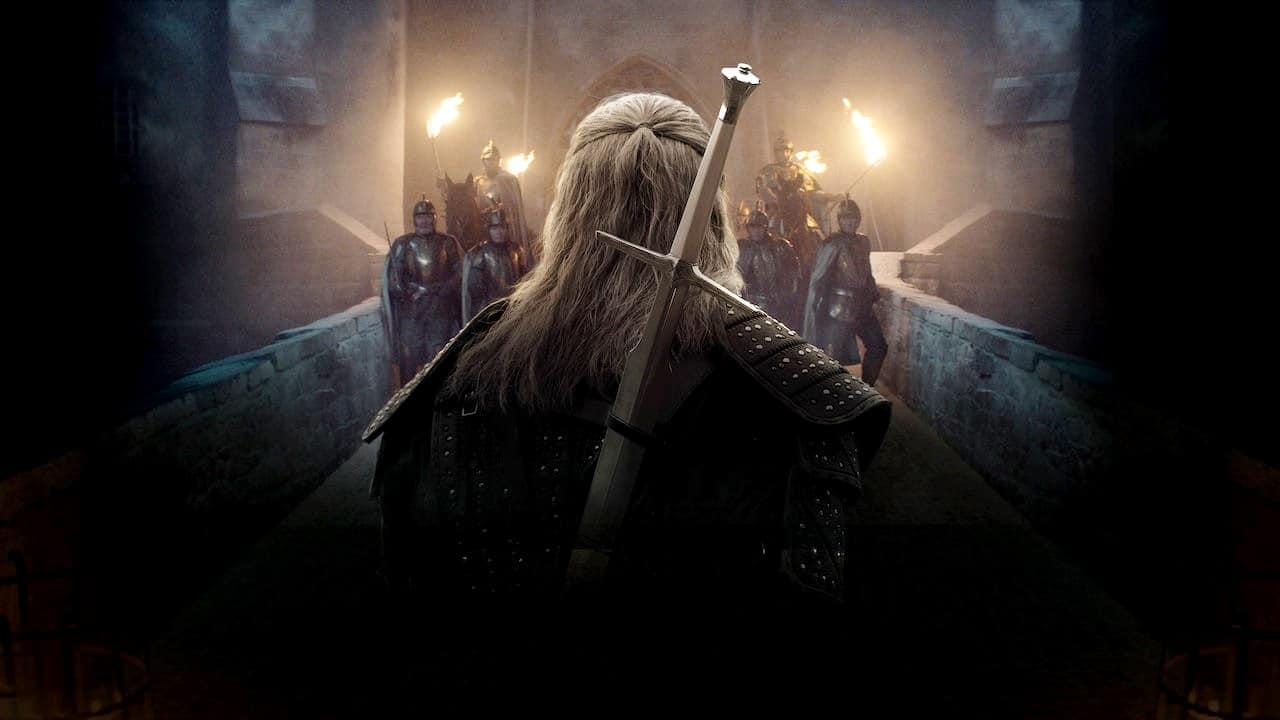 Geralt de Rivia, protagonista de The Witcher, de frente com vários soldados co tochas nas mãos