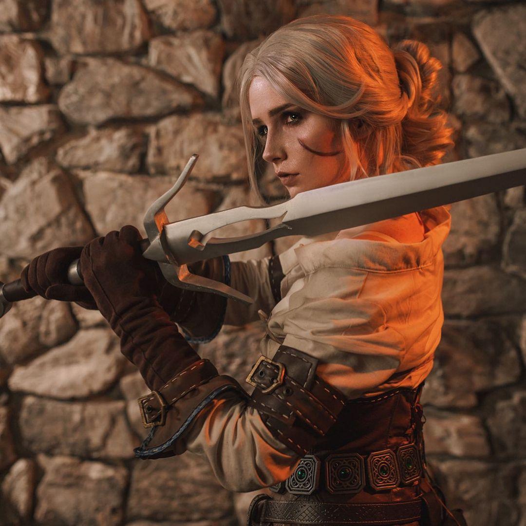 Imagem do cosplay da personagem Ciri, de The Witcher 3, fazendo uma pose e segurando uma espada
