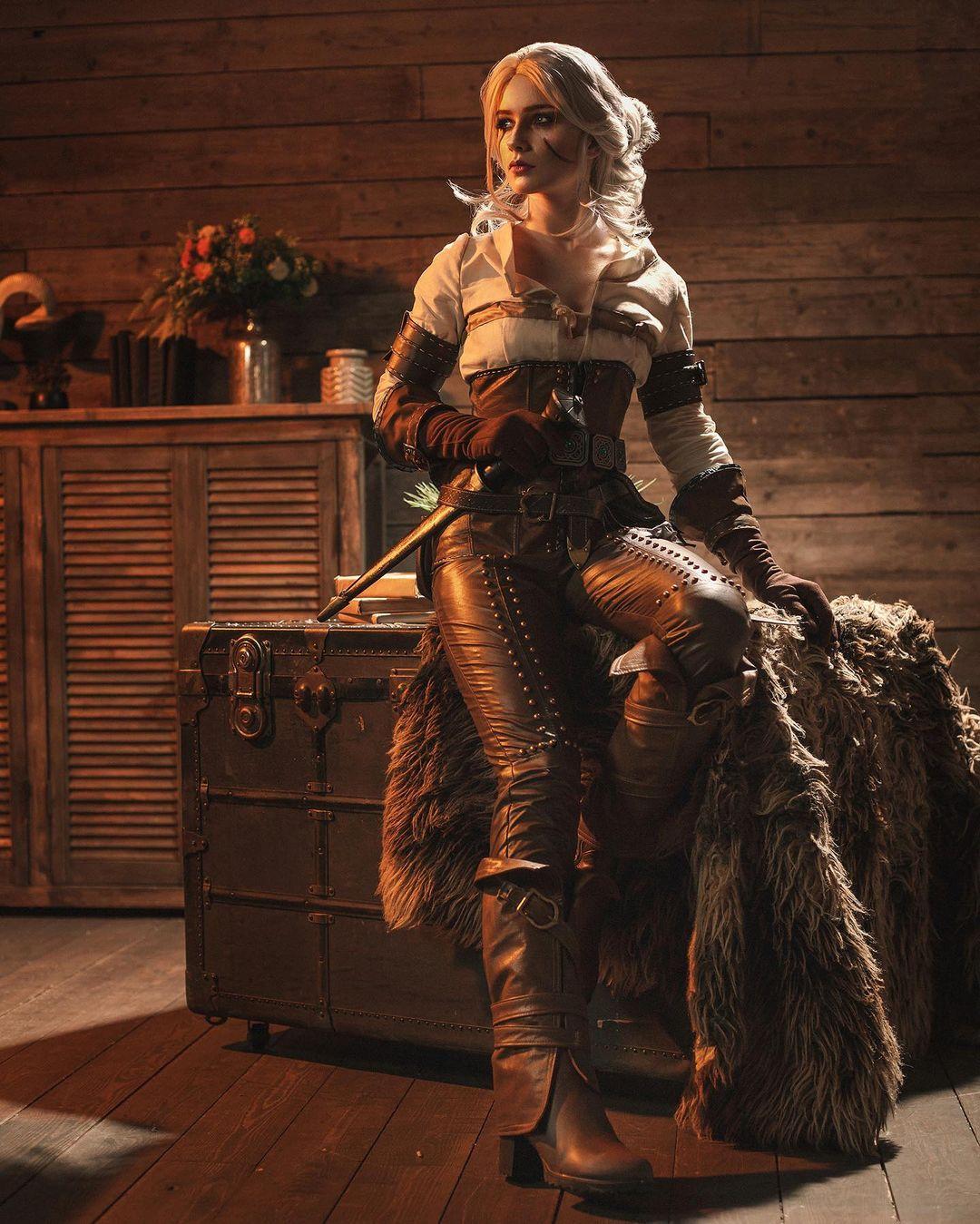 Imagem do cosplay da personagem Ciri, de The Witcher 3, sentada em cima de um baú
