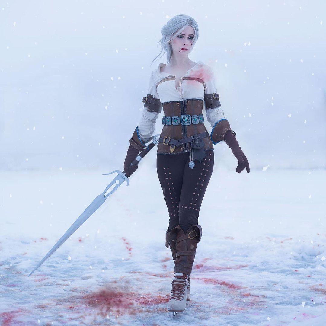 Imagem do cosplay da personagem Ciri, de The Witcher 3, de frente segurando uma espada
