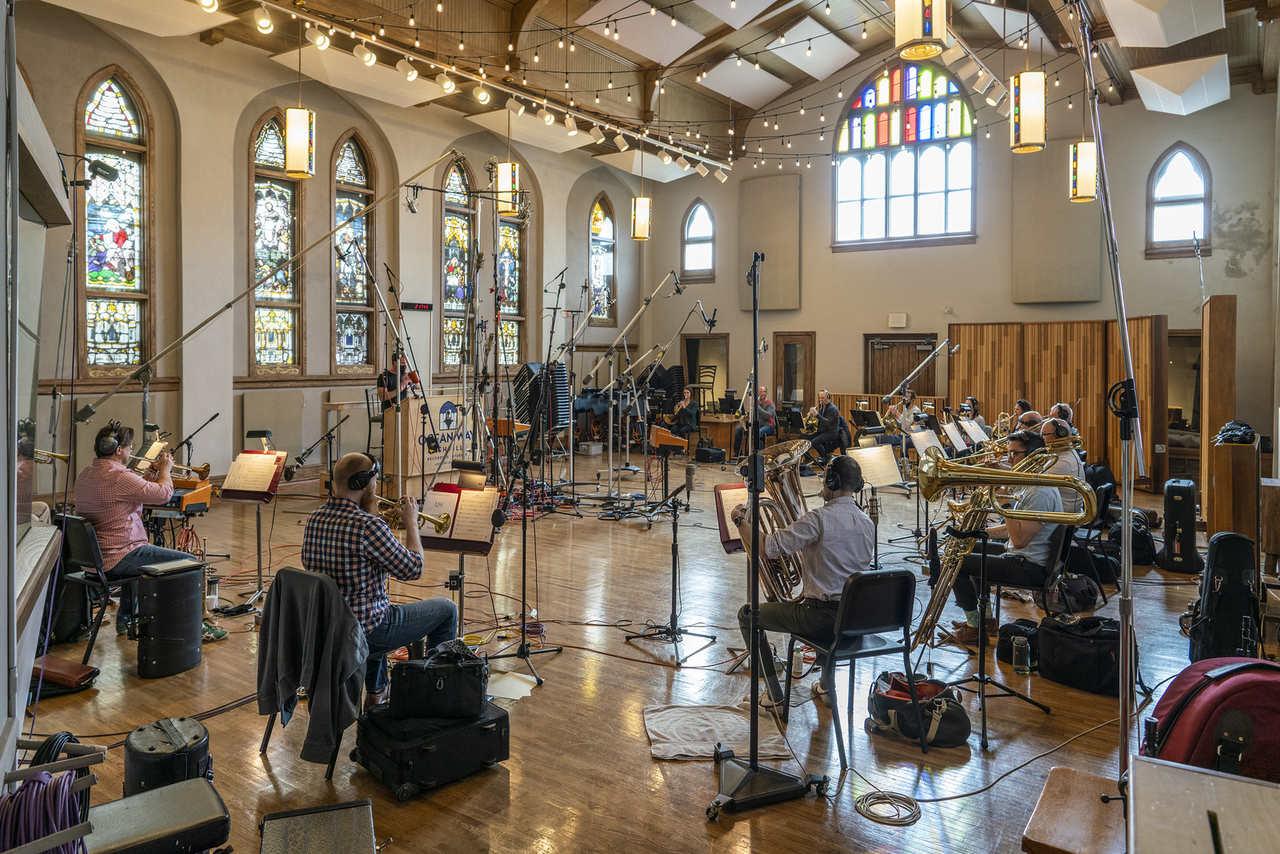 Imagem de uma sessão de gravação orquestral do novo Ratchet & Clank com diversos músicos tocando instrumentos
