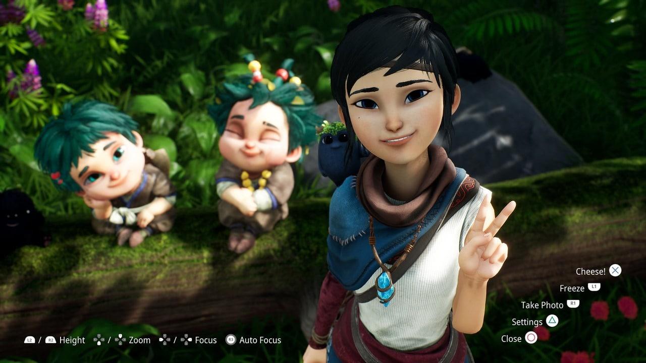 Imagem de capa do Modo foto de Kena: Bridge of Spirits com a protagonista fazendo uma pose e outras duas personagens no fundo